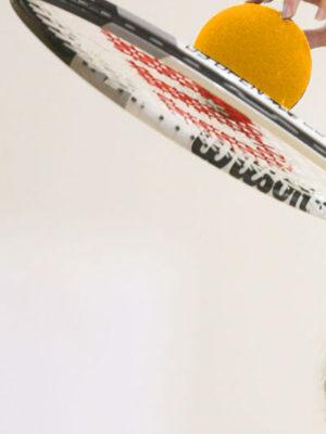 Sur fond blanc, on y vot une raquette de tennis avec une balle jaune dessus tenus par une main
