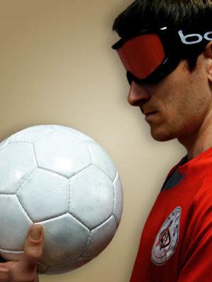 Photo d'un joueur de torball, il s'appelle Cédric, il porte le Tee-shirt du club ANICES qui est rouge, il met en avant le ballon de torball et porte le masque de protection