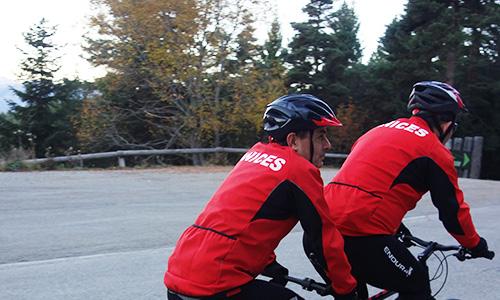 photo de deux cycliste en tandem avec leur veste de l'anices.Ils sont entrain de pédalé en fond on aperçois la nature avec des sapins