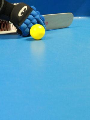 Sur une table de showdown bleu, on y voit une main dans un gant de protection, tenant une raquette de showdown, avec une balle jaune