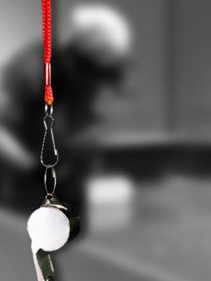 En second plan une photo en noir et blanc dans laquelle on aperçois la silhouette d'un joueur de showdown, au premier plan, un sifflet avec un cordon rouge