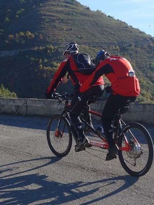 En premier plan il y a deux cyclistes sur un tandem aux couleurs de l'ANICES et en second plan on y voit des collines.